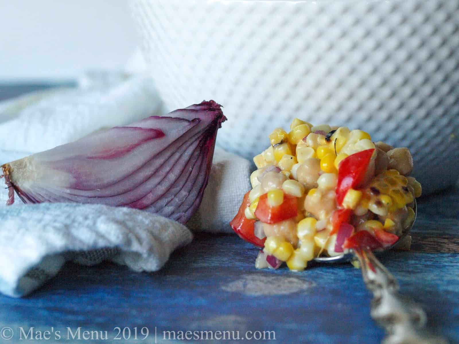 A large spoon full of chickpea & grilled corn salad next to a red onion.