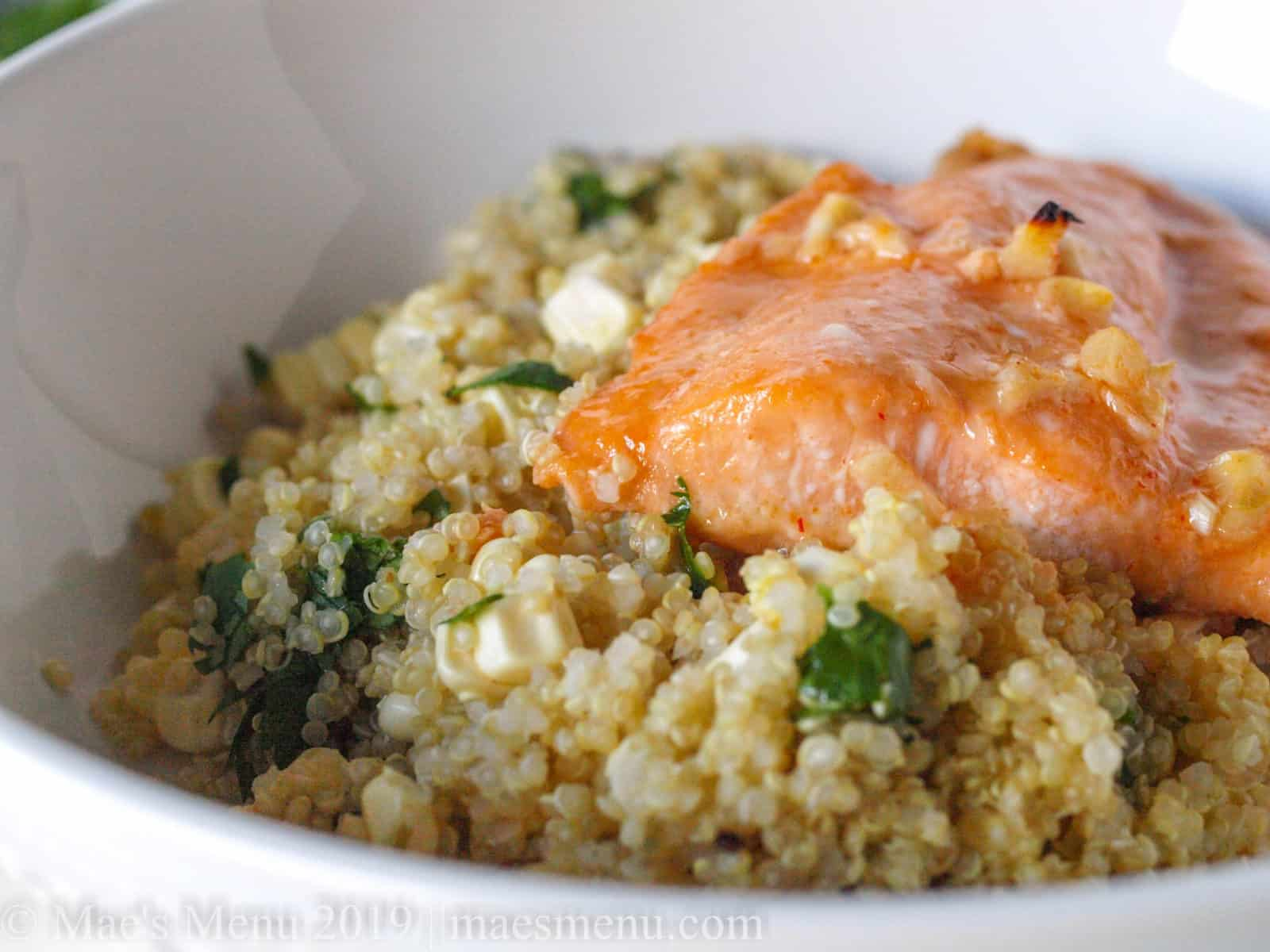 Up close of easy baked salmon on a bed of quinoa salad.