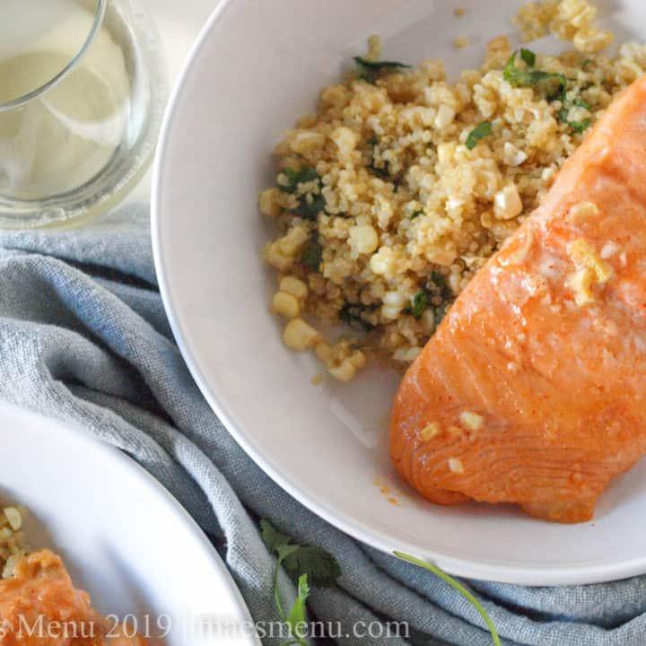 Two bowls of sriracha lime salmon next to fresh corn & quinoa salad.