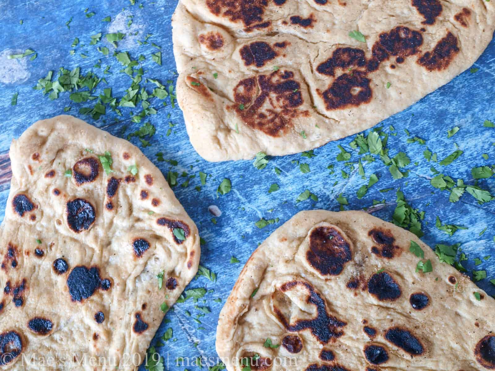 3 whole wheat naan sitting on a blue wooden background.