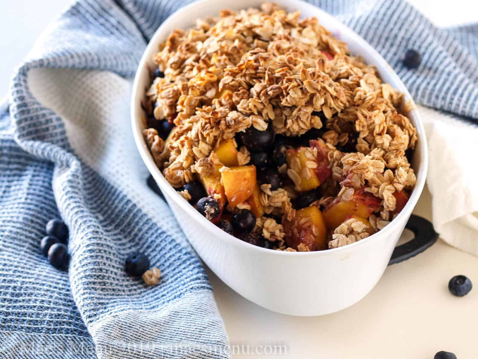 White baking dish of healthy blueberry peach crumble.