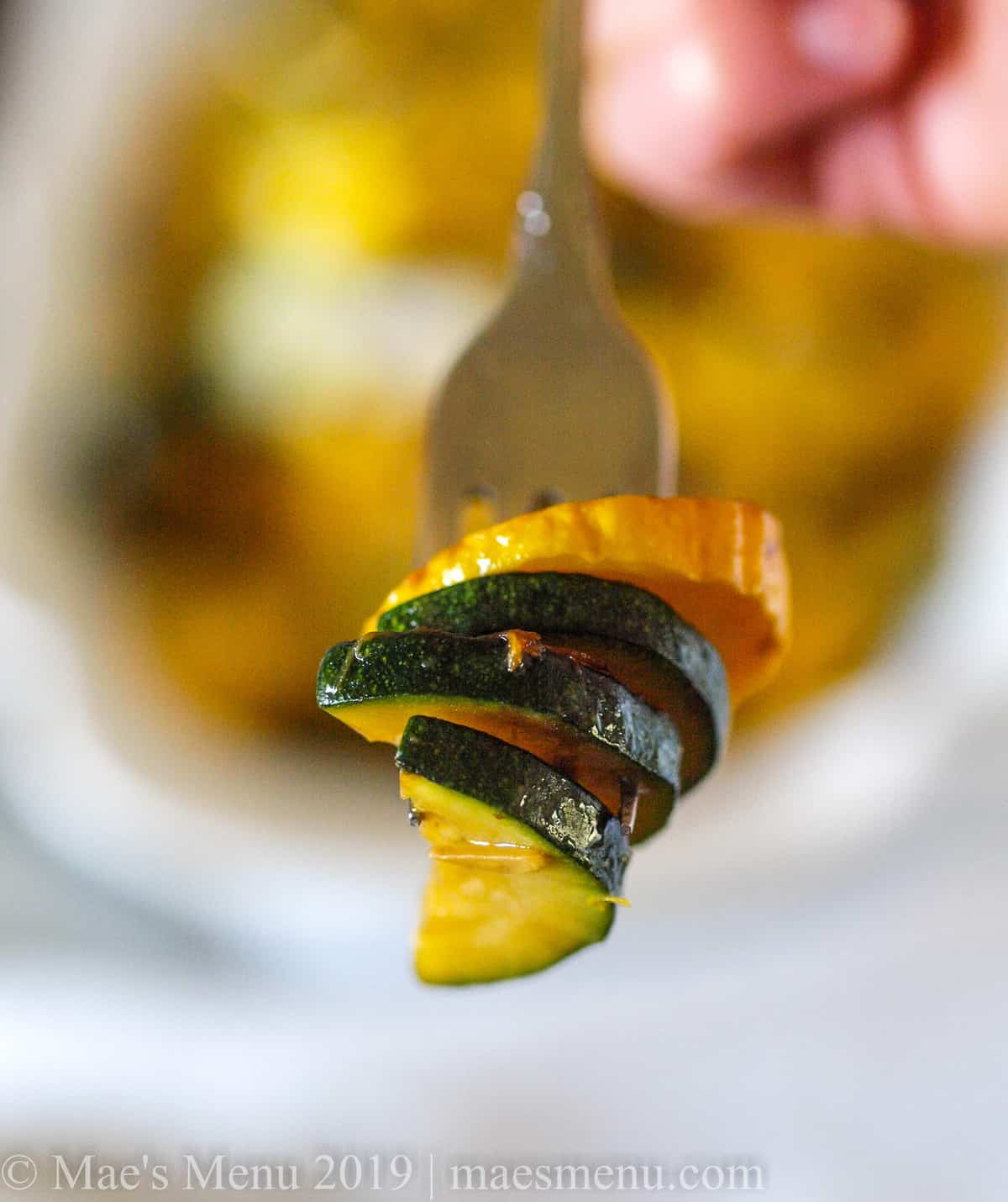 Sauteed zucchini and yellow squash on a fork.