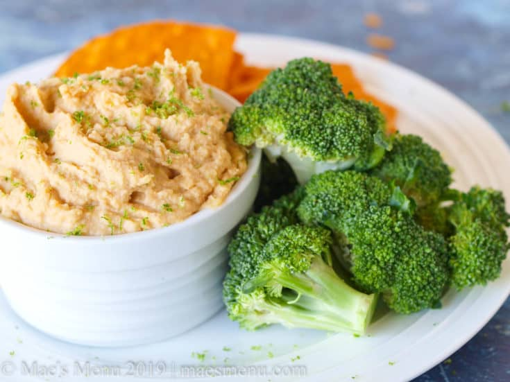 Small dish of curry hummus with chips and broccoli.