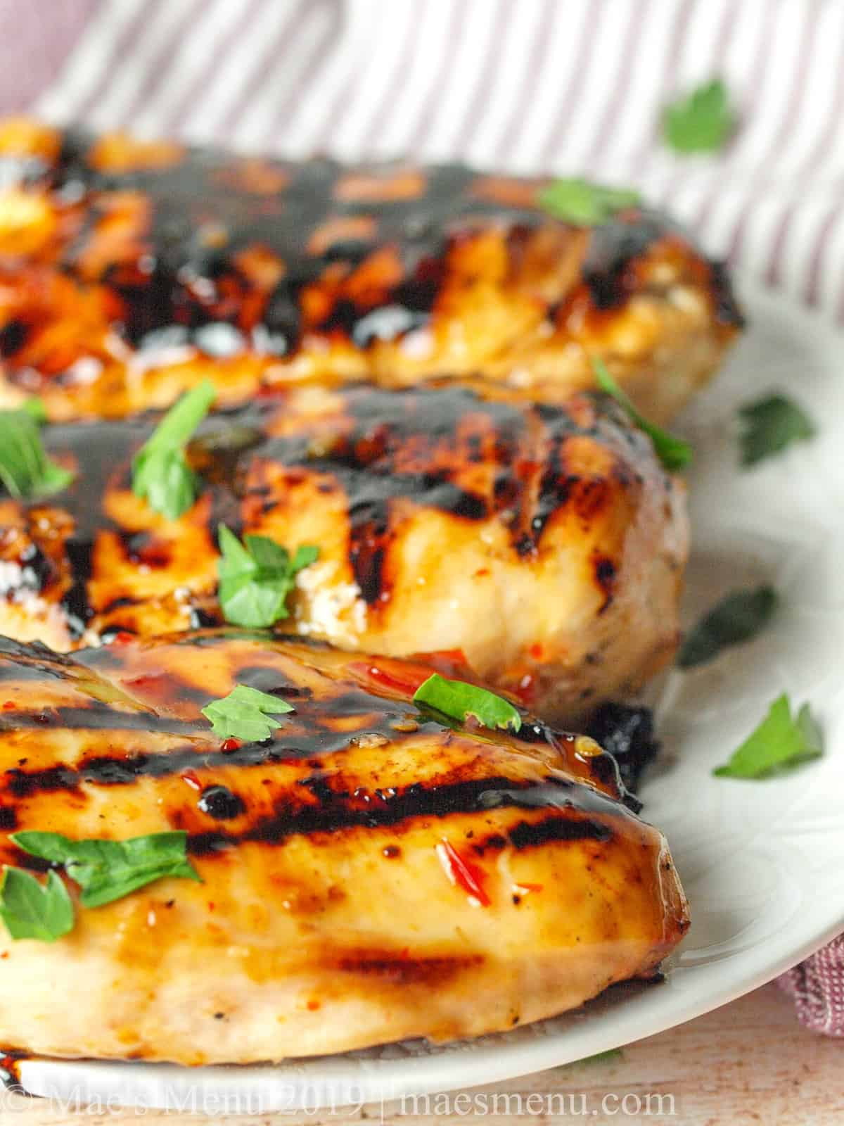 A side shot of 3 grilled sweet chili chicken breasts.