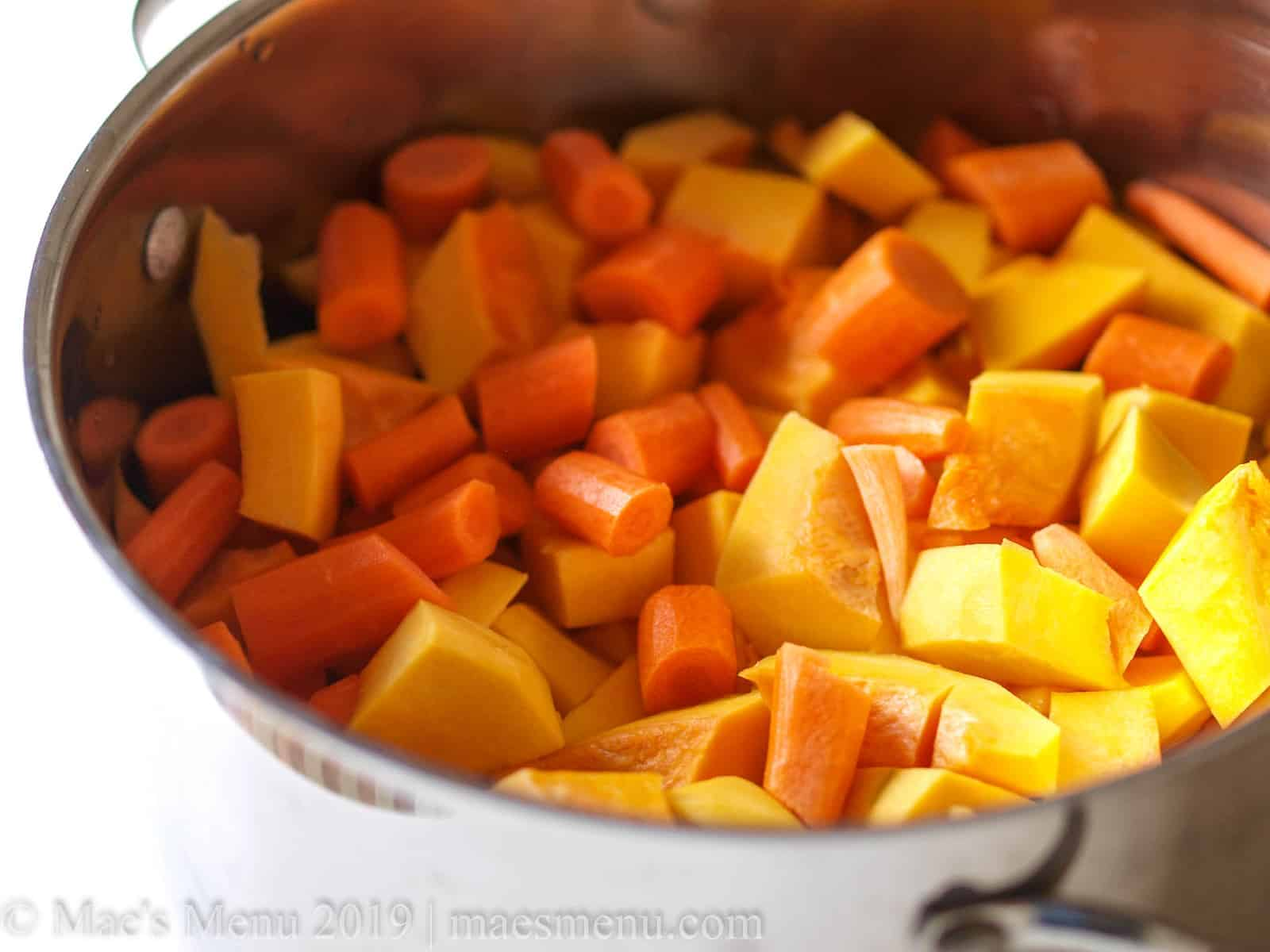 The raw ingredients for super easy butternut squash soup. cut up and in a large stock pot.