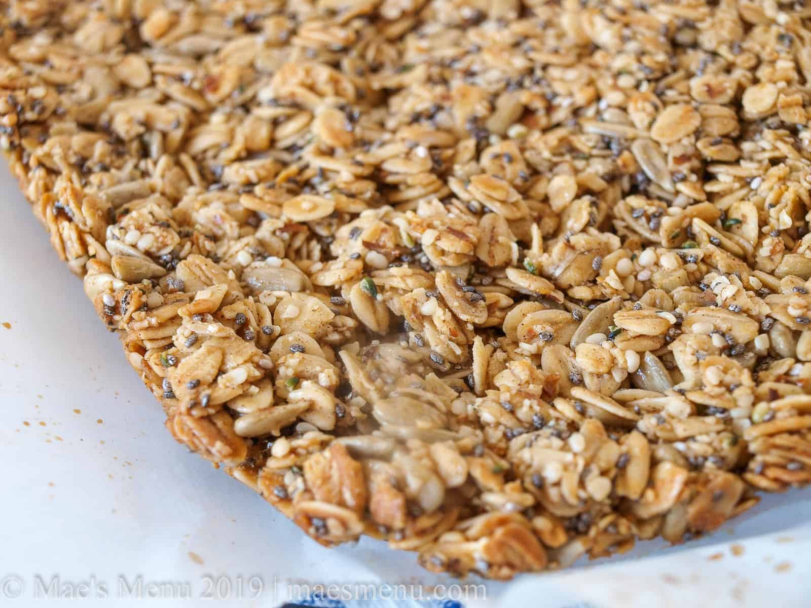 A corner of a large sheet of pumpkin spice granola bars before they are sliced.