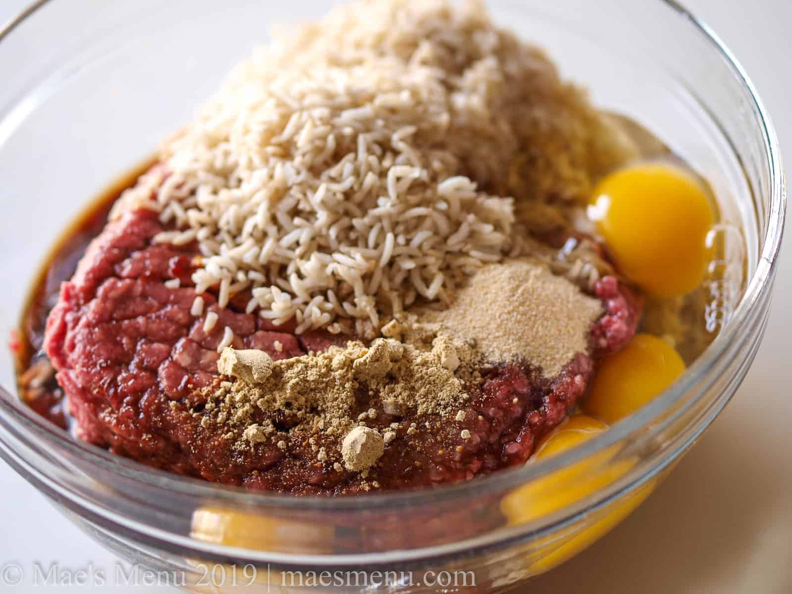All the raw ingredients for a teriyaki meatloaf in a large glass mixing bowl