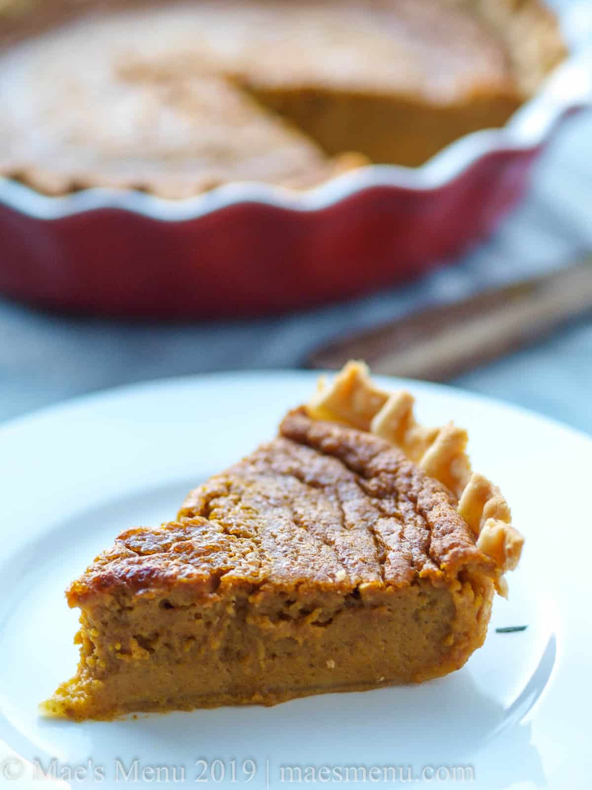 A piece of pumpkin pie without evaporated milk in front of a pie pan of pumpkin pie