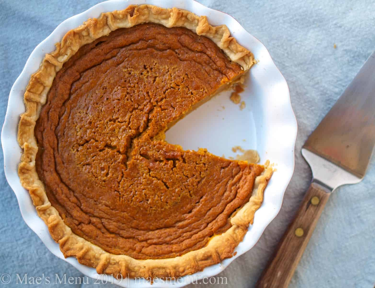 A pumpkin pie with a piece taken out