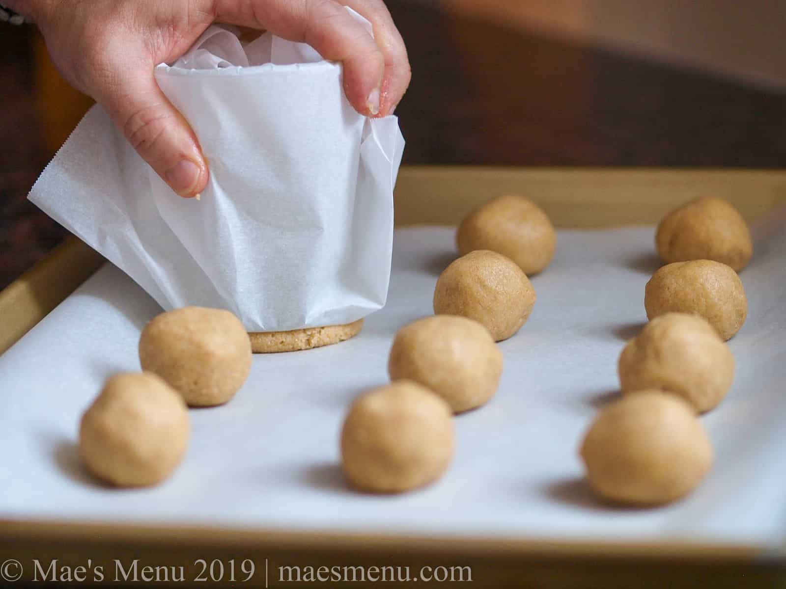 Smushing sugar cookie balls to make round sugar cookies.
