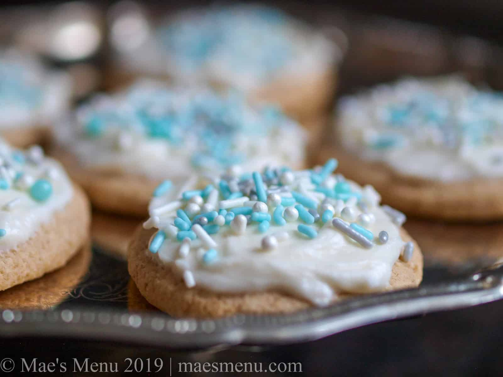 High altitude sugar cookies with vanilla cream cheese frosting. on a silver platter