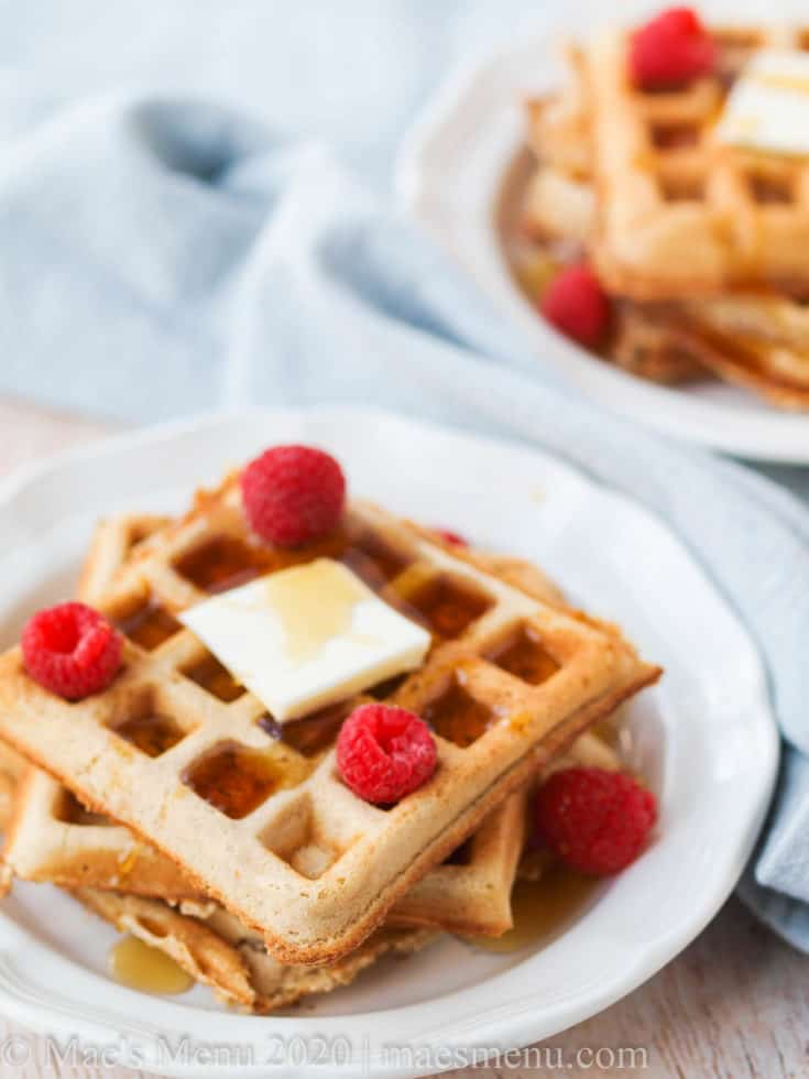 Two plates full of fluffy whole wheat belgian waffles.