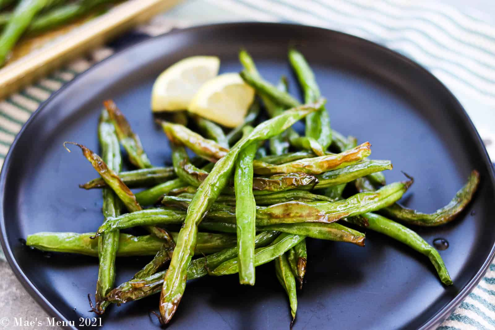 A small serving of air fryer green beans on a black plate