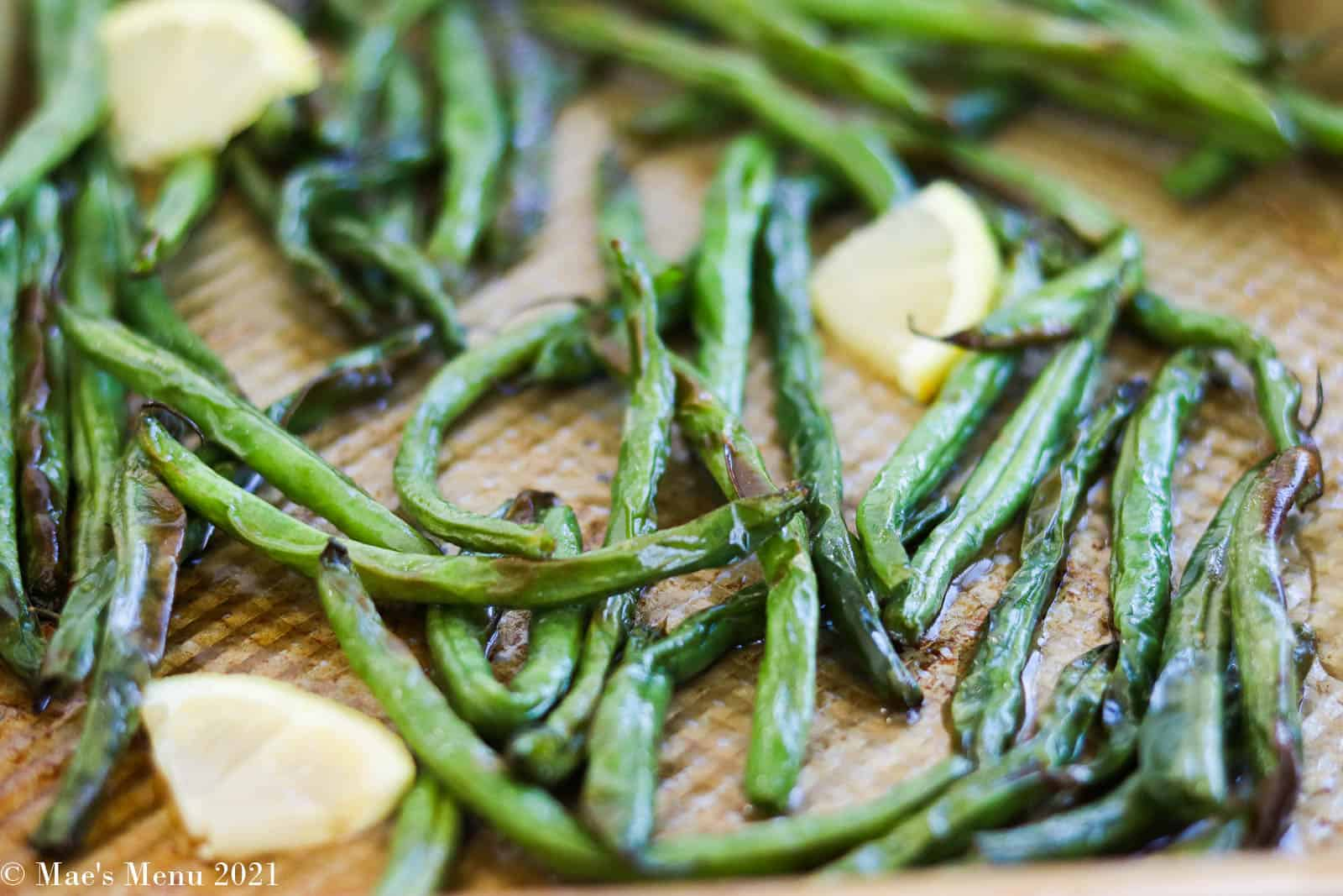 Air fryer green beans on a baking sheet with lemons