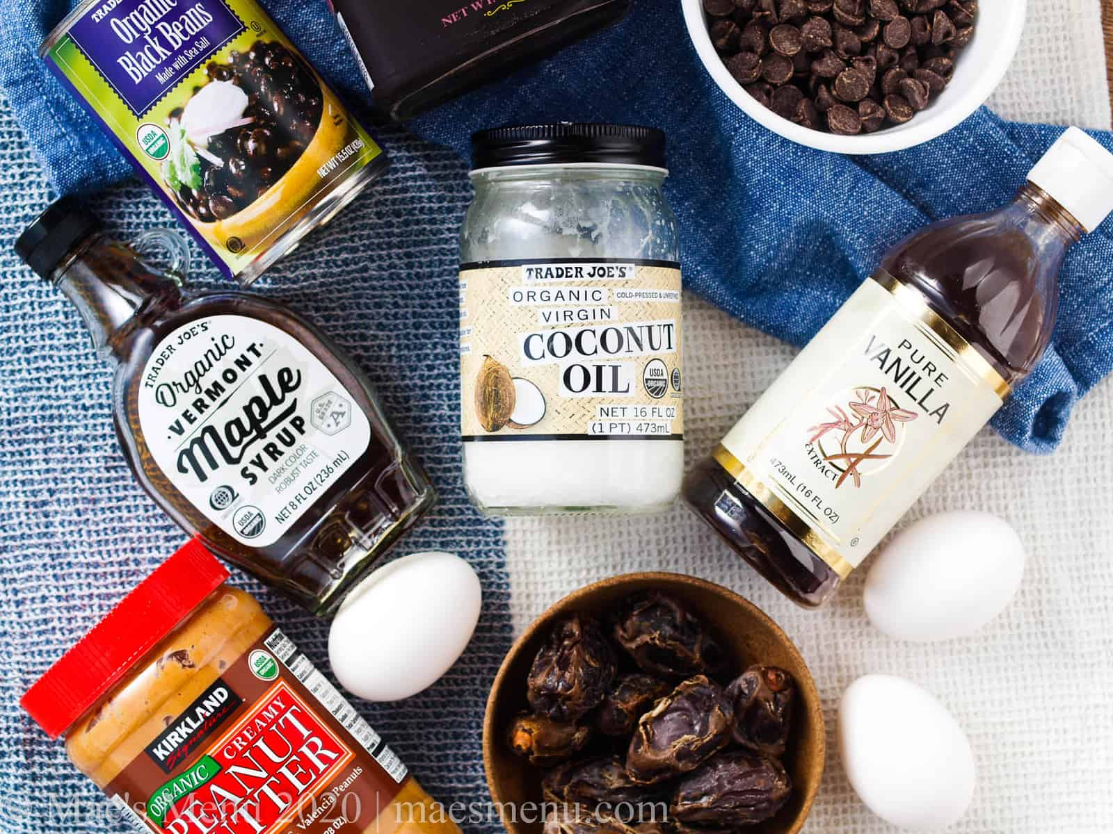The ingredients for fudgy date brownies: peanut butter, maple syrup, eggs, dates, cocoa powder, coconut oil, and more.