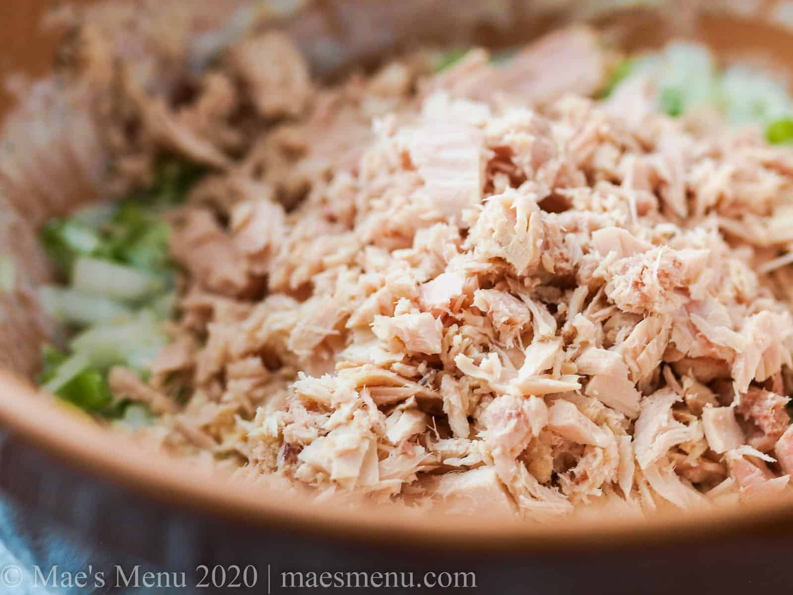 A mixing bowl full of ingredients for tuna macaroni salad.