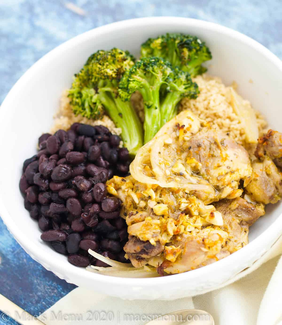A bowl of cuban mojo chicken with black beans, couscous, and broccoli.