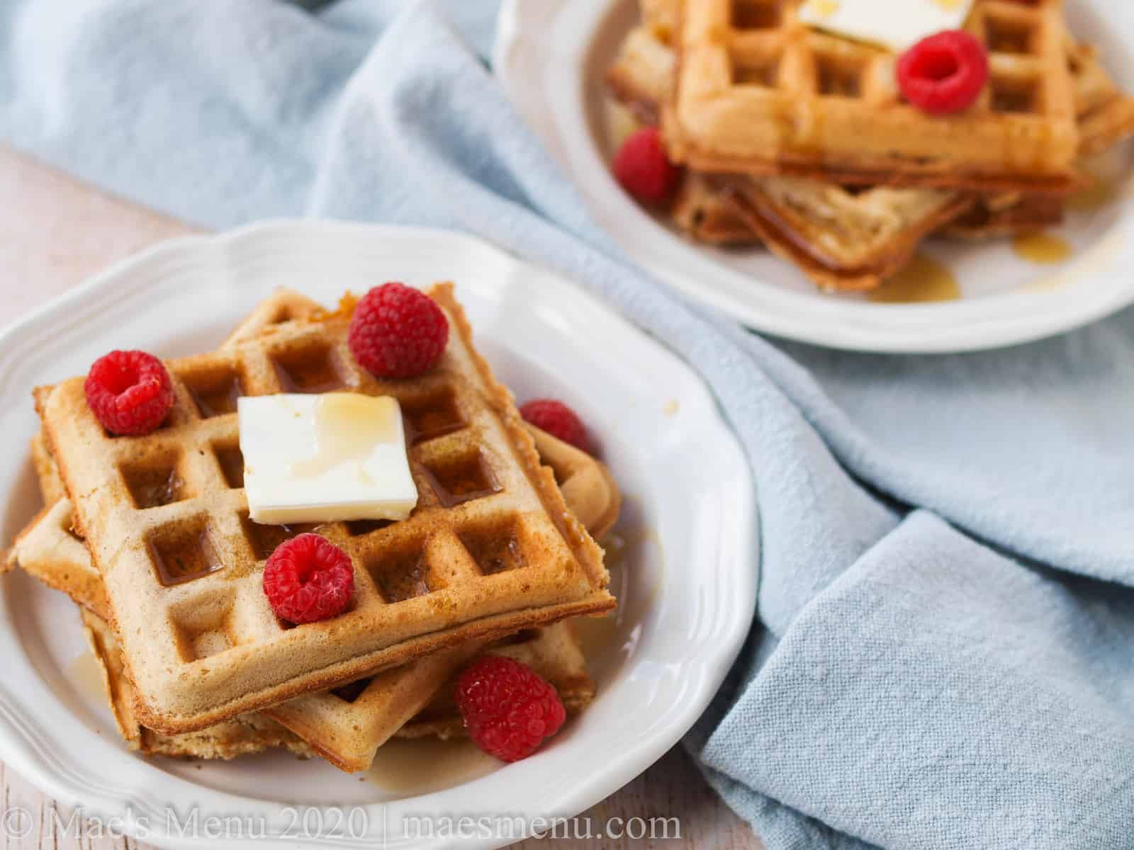 Two small plates of waffles with raspberries, butter, and syrup.