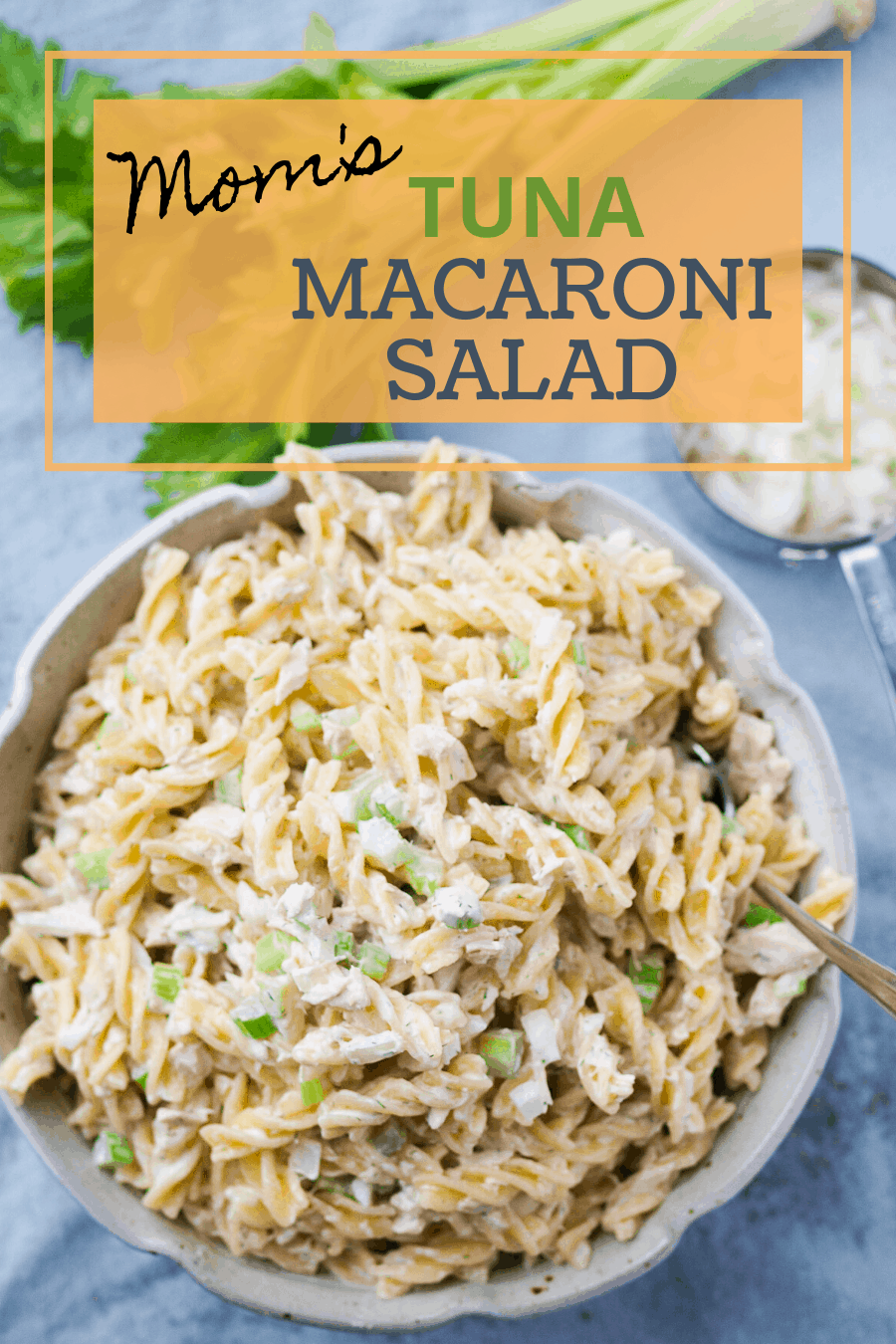 A pinterest pin for tuna macaroni salad. A large bowl of tuna macaroni salad in front of diced onions, a stalk of celery.