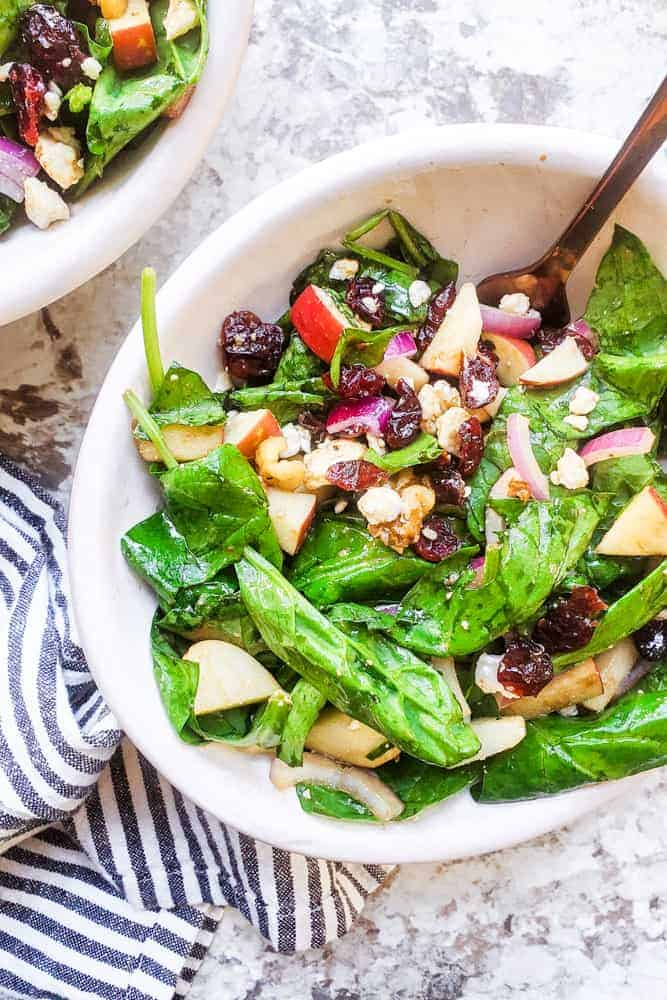 A large white bowl of spinach apple salad with a fork and striped dish towel.