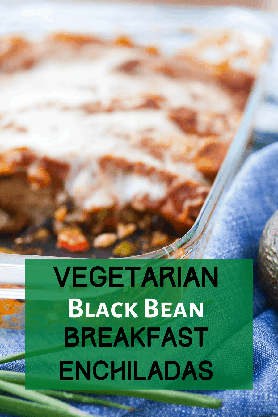 A pan of black bean enchiladas next to a towel, avocado, and green onion. This picture is my pinterest pin for the recipe.
