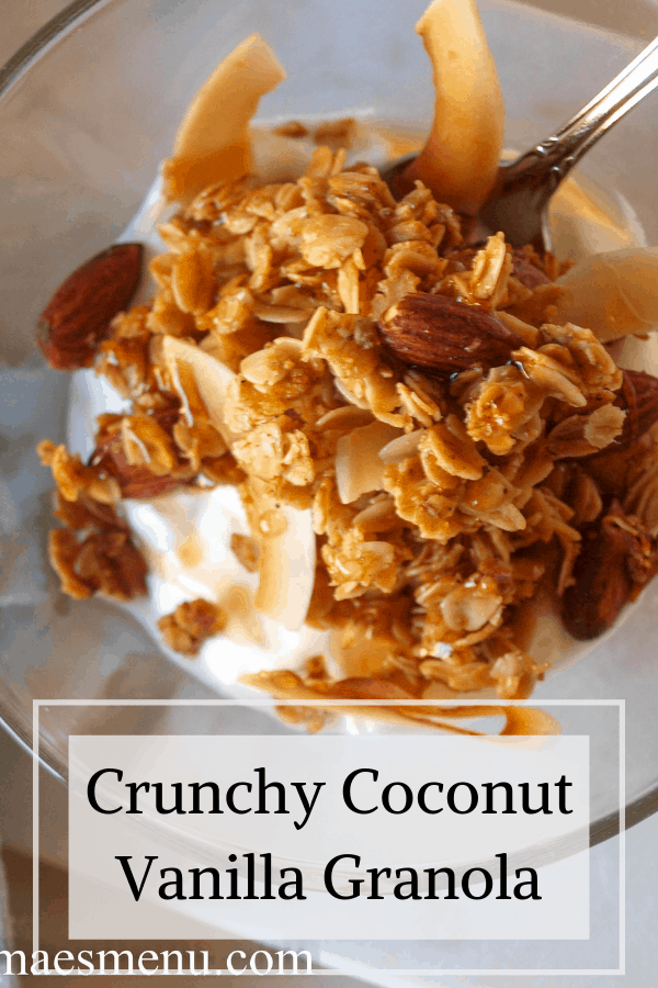 A pinterest pin for crunchy coconut vanilla granola -- an up close shot of granola over yogurt in a clear bowl.