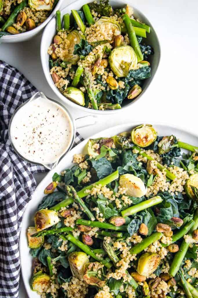 1 large and 2 small bowls of healthy crunchy quinoa salad next to a small ramekin of dressing and a brown checkered towel