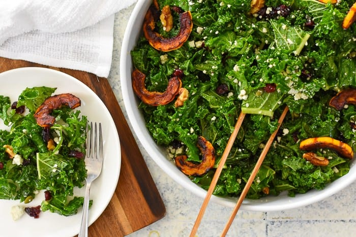 A large bowl of kale salad next to a smaller plate of salad.