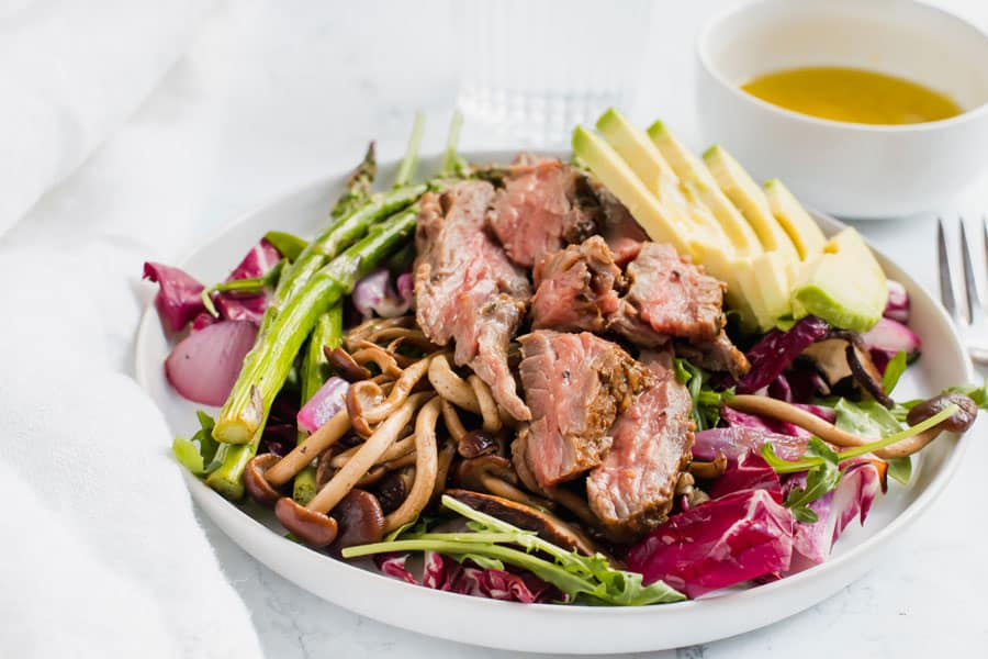 A white bowl of grilled steak salad with avocado next to a dish of dressing