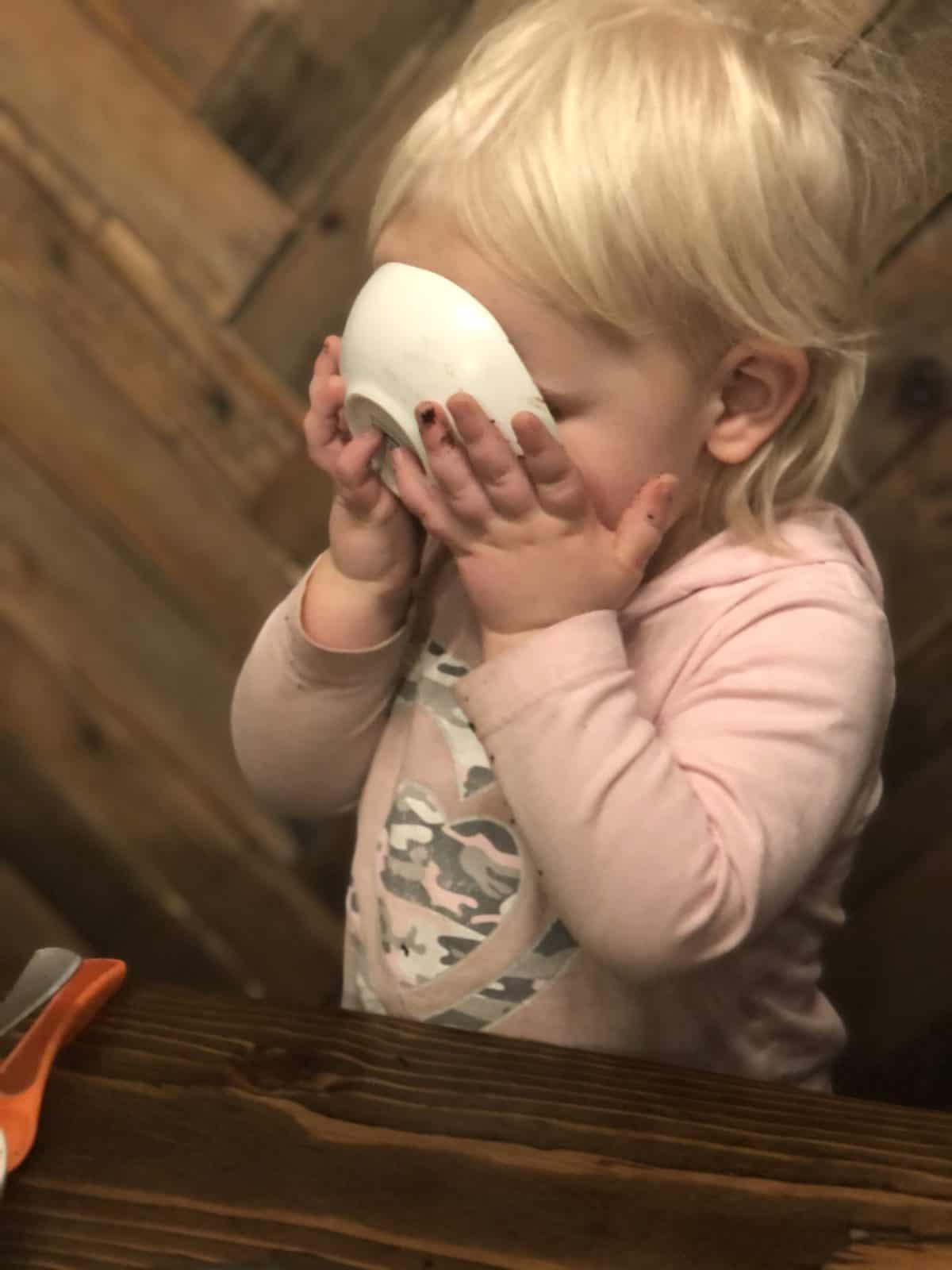 A little girl enjoying her food.