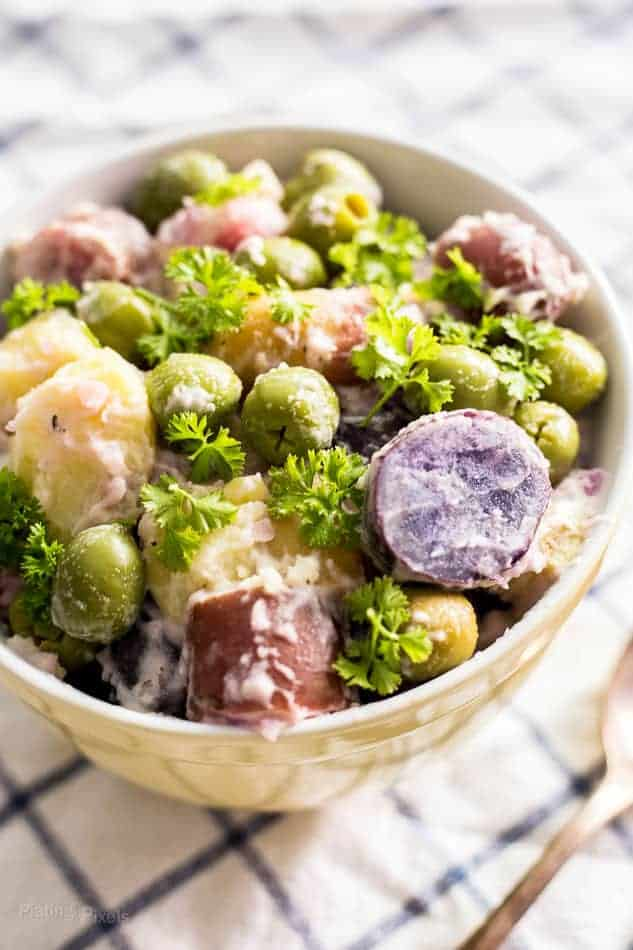 An up-close shot of a white bowl of fingerling potato salad.
