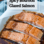 A pinterest pin for spicy bourbon glazed salmon. A tray of salmon sits in the background.