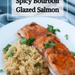 A pinterest pin for spicy bourbon glazed salmon. A fillet of salmon sits on top of couscous