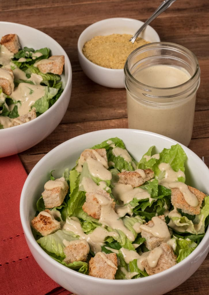Two white bowls of vegan Caesar salad next to a cup of dressing and a small bowl of nutritional yeast.