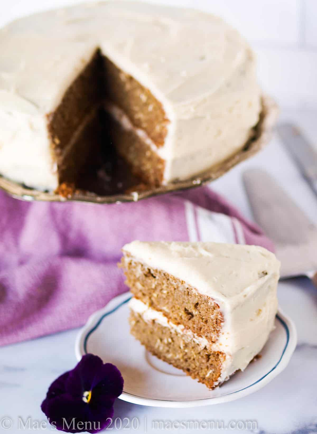 A cake stand with a banana oatmeal cake and a slice of cake in front of it.