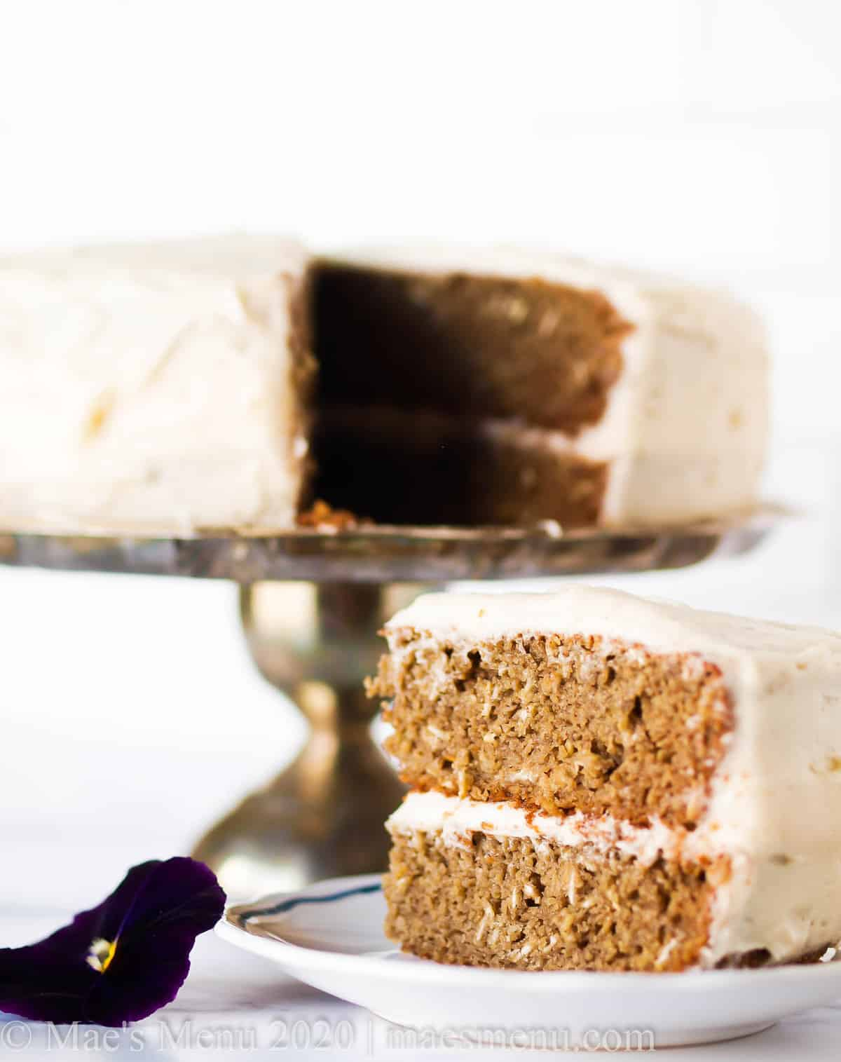 Homemade banana cake on a stand next to a slice of cake on a small dish