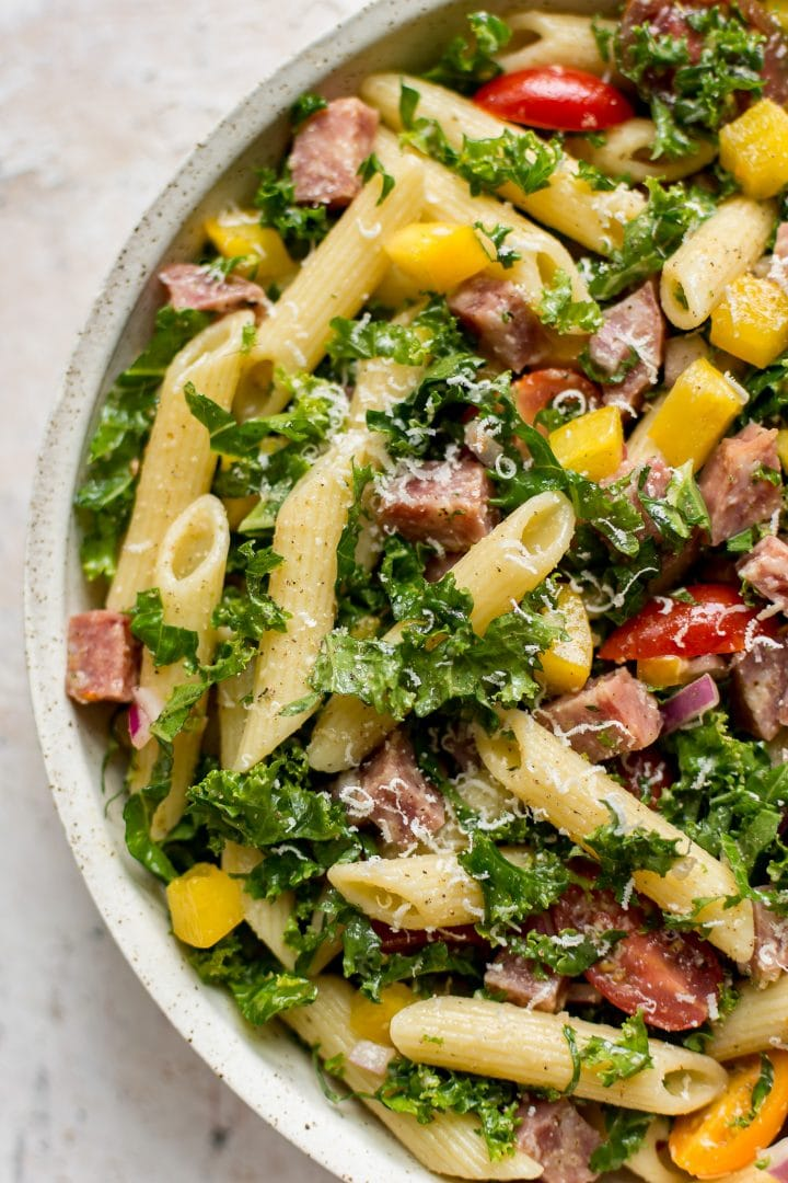 An upclose shot of kale pasta salad in a stone colored bowl
