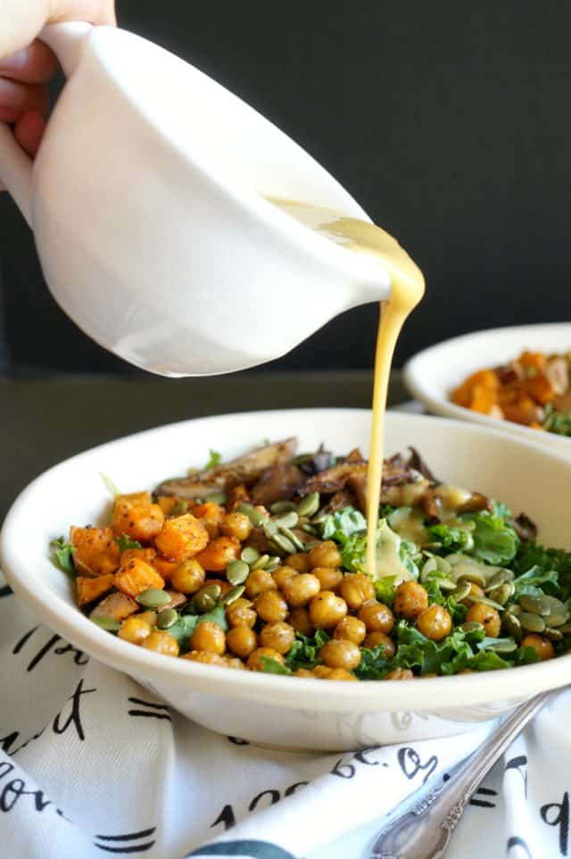 A large bowl of salad with a cup of dressing pouring over top it.