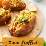 A pinterest pin for taco stuffed sweet potatoes with the sweet potatoes sitting on a wooden board next to lemon, avocado, and cilantro.