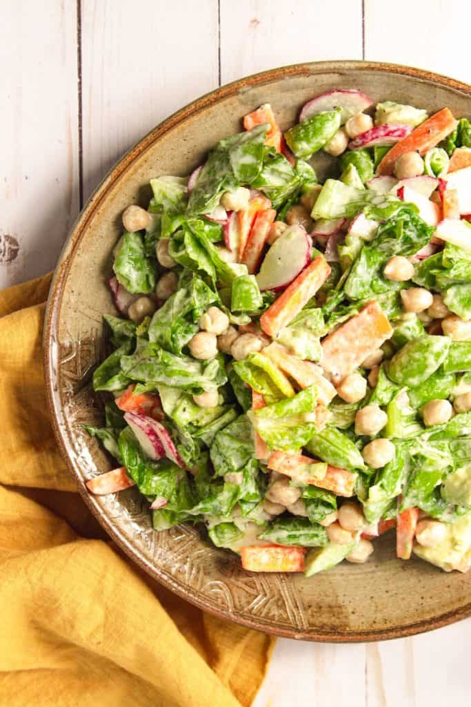 A large tan plate of vegan chopped salad sitting on top of a yellow towel.