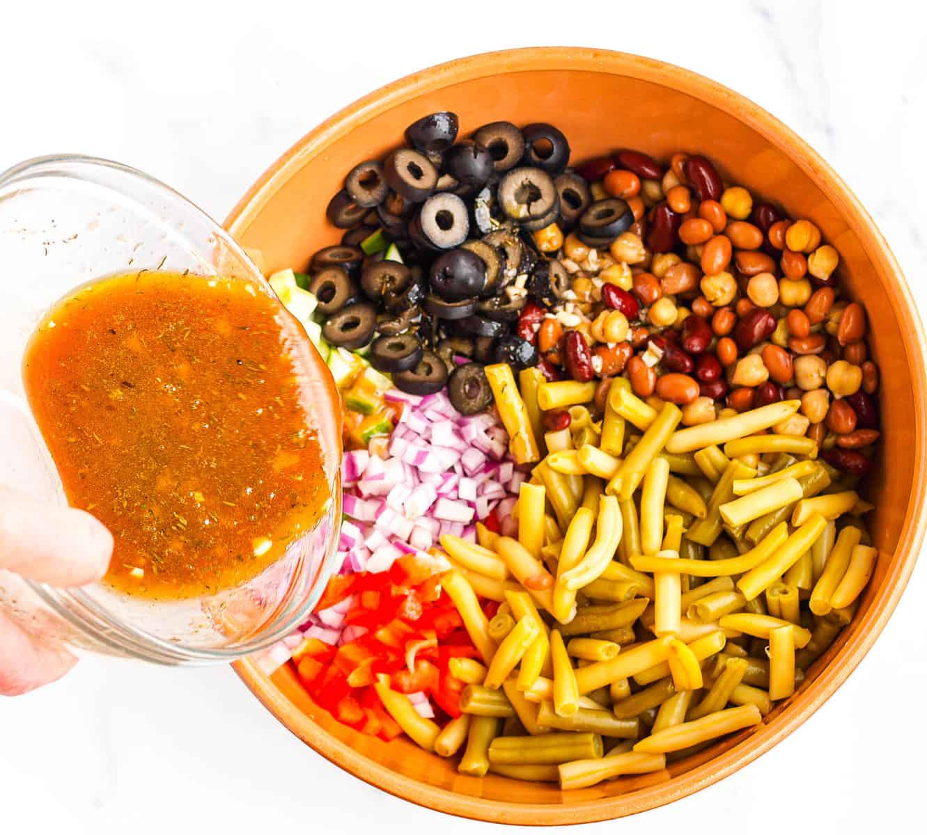 Pouring the dressing over the veggies and beans
