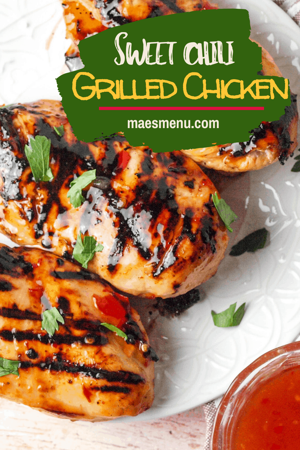 A pinterest pin for sweet chili grilled chicken with an overhead shot of the chicken on a white platter sitting next to a towel and cup of chili sauce.