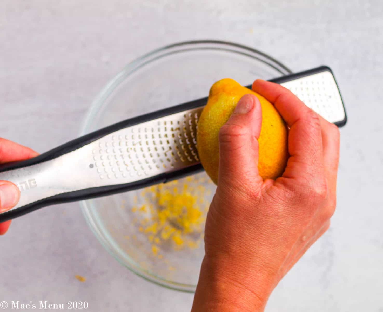 Zesting a lemon on a microplane zester over a clear bowl.