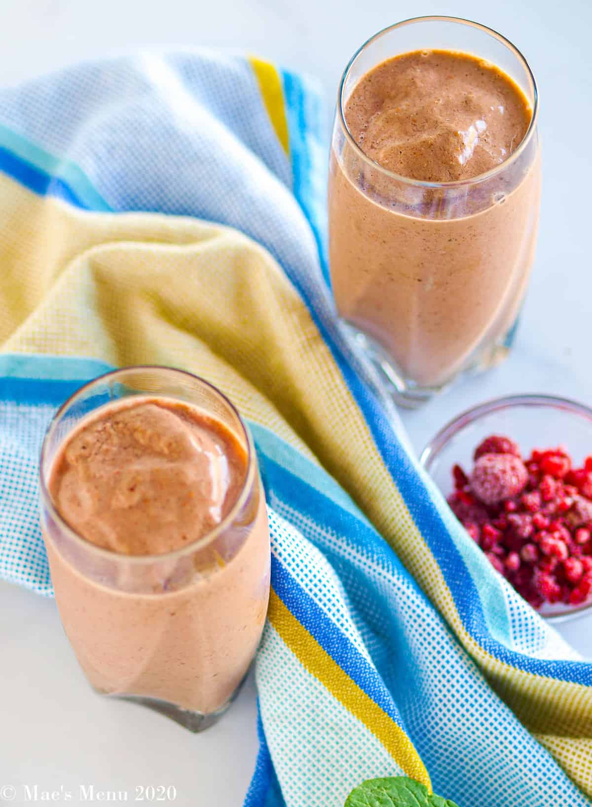 Two large glasses of creamy raspberry smoothie next to a small dish of frozen raspberries. between the glasses sits a blue and yellow dish cloth.