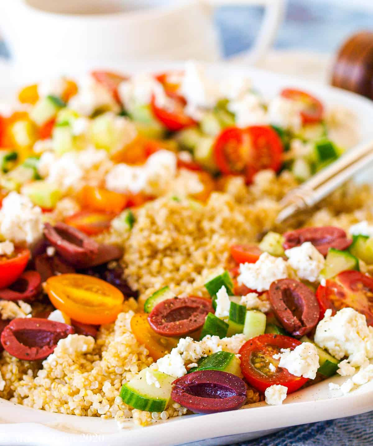 A side shot of a platter of Greek quinoa salad with a pitcher of salad dressing behind it and a pepper mill on the back right of the platter.