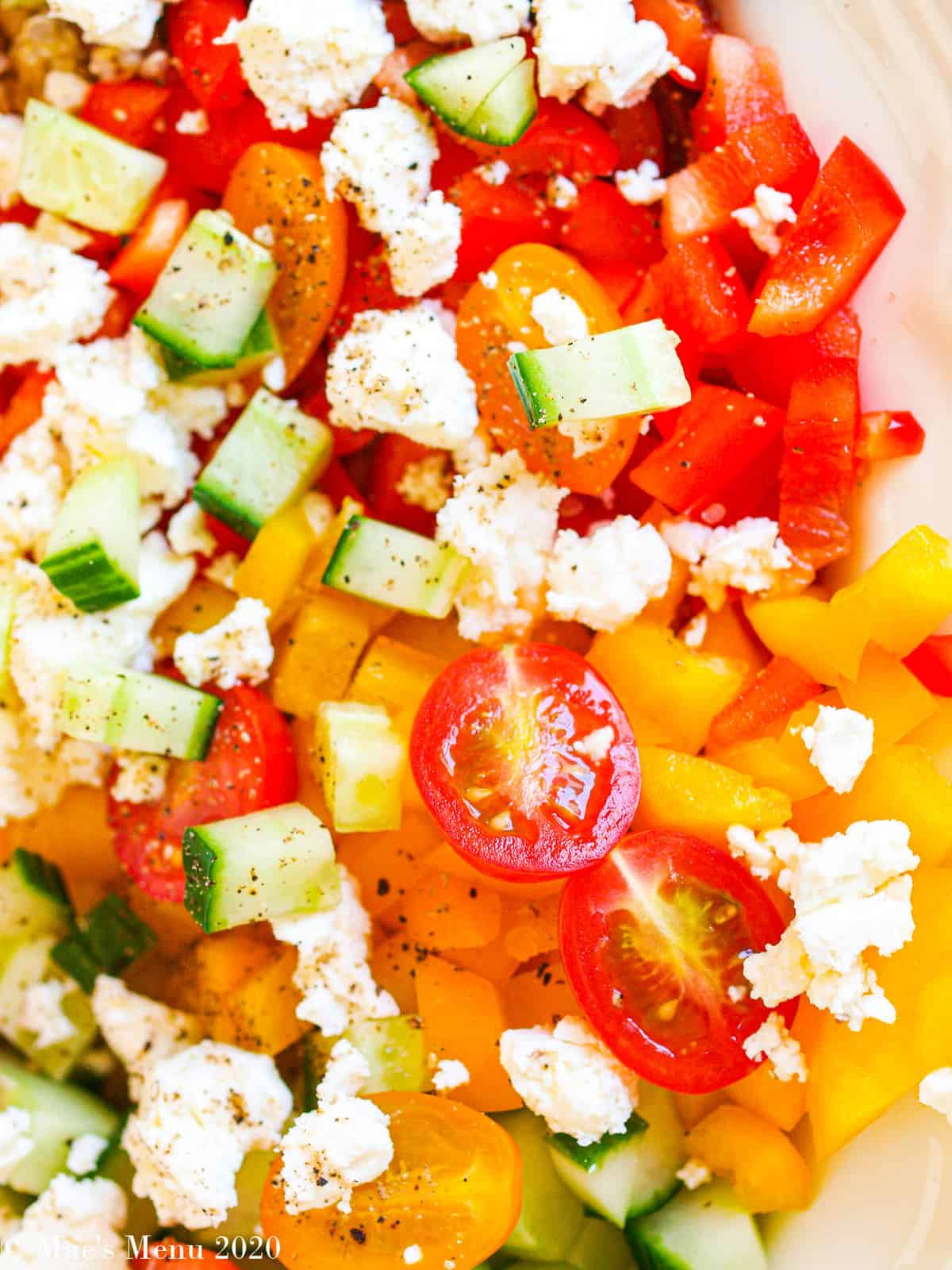 An up-close overhead shot of chopped sweet peppers, cucumber, halved cheers, and feta chese