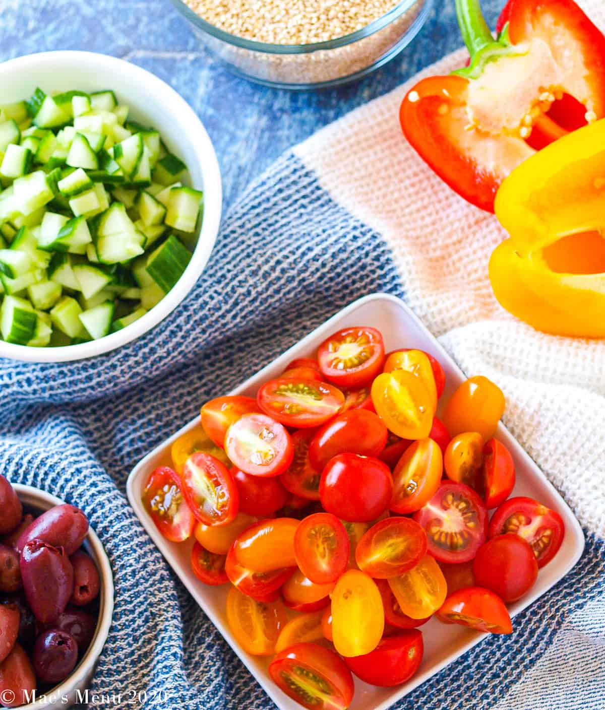 Small plates and bowls of sliced tomatoes, chopped cucumber, kalamata olives, and two sweet peppers cut in half