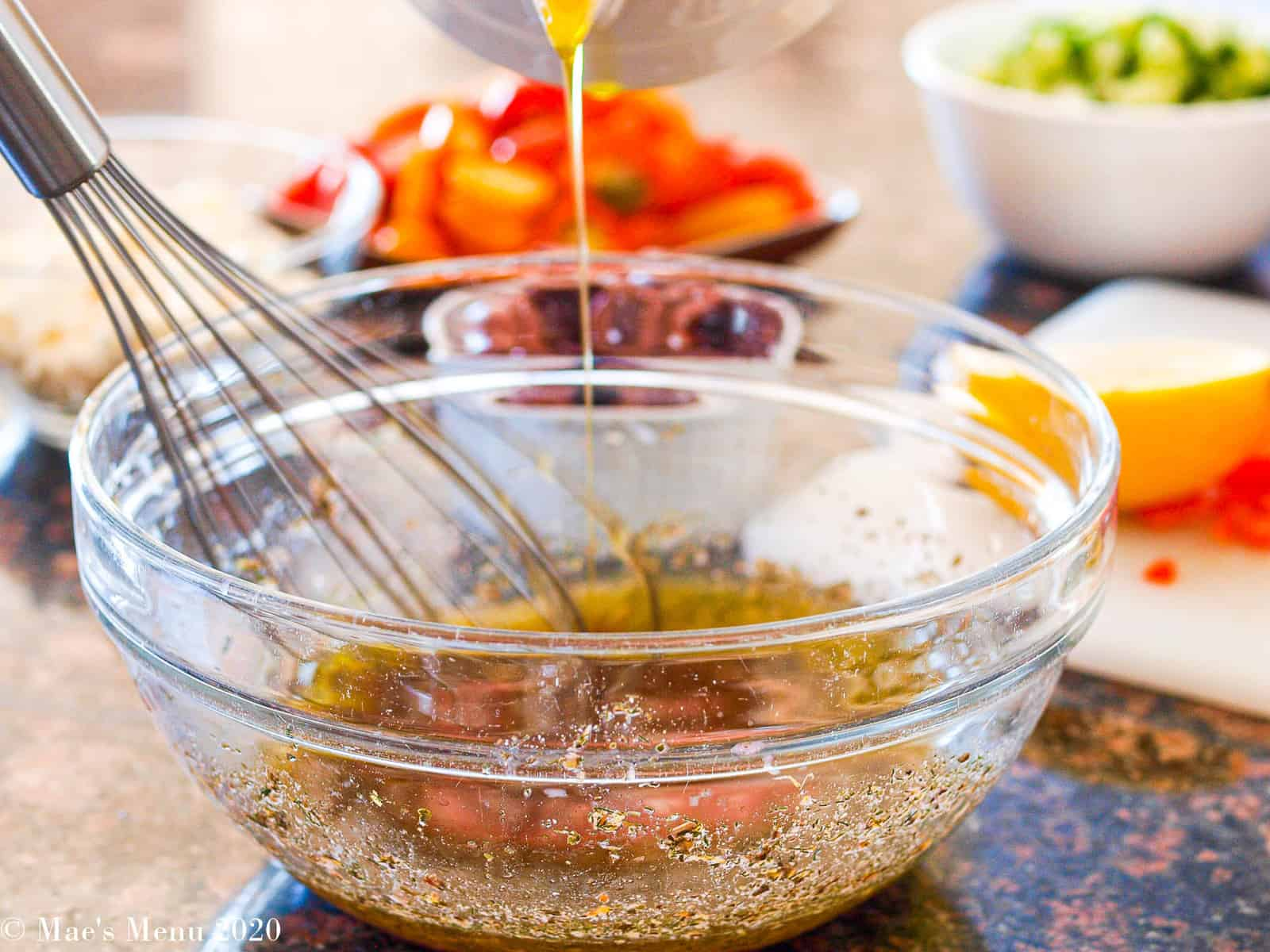 A clear mixing bowl with a whisk and salad dressing in it. Olive oil is being poured in the bowl from above