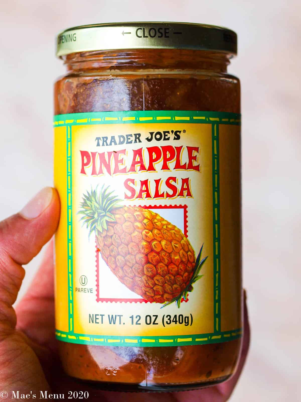 An up-close shot of a bottle of pineapple salsa.