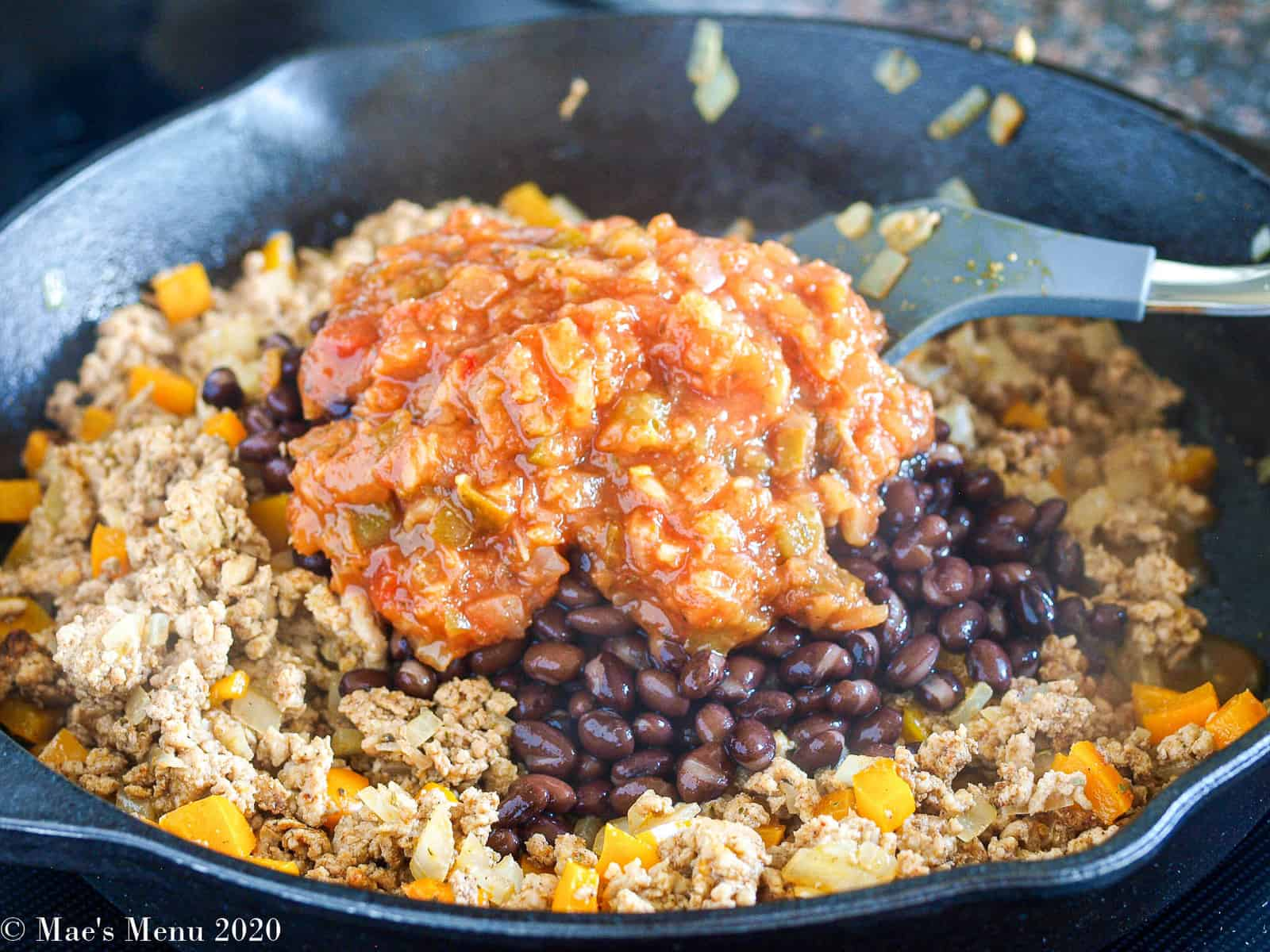 Adding the salsa and beans to the skillet with the turkey